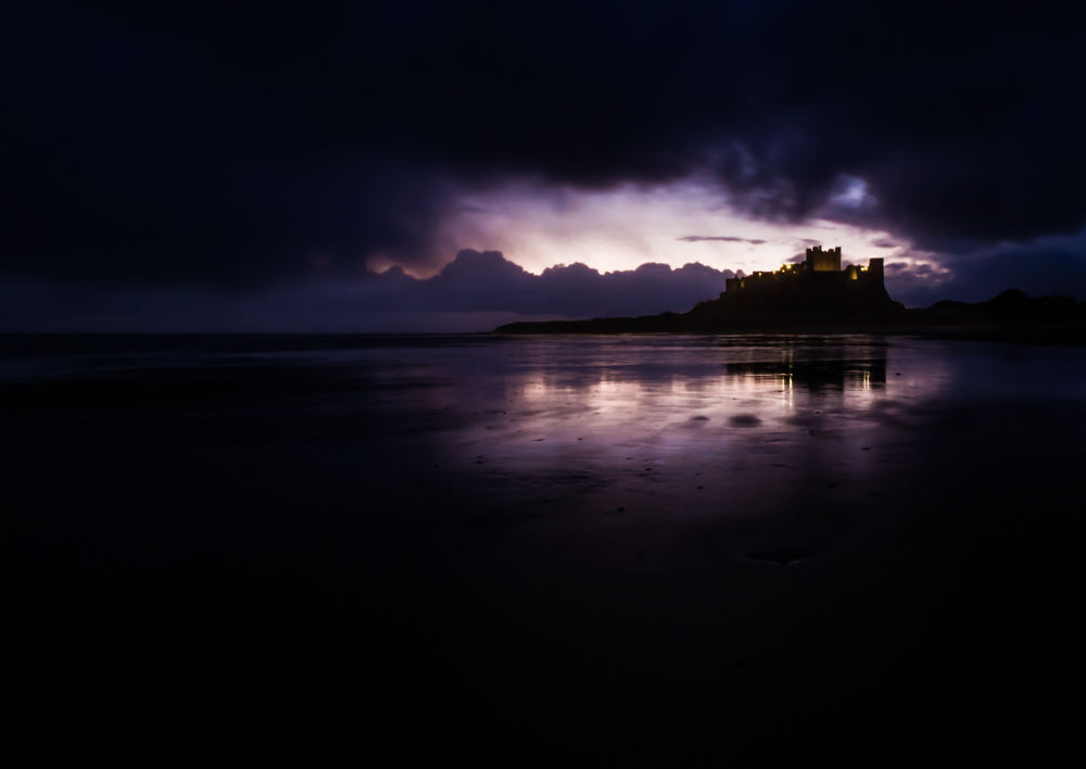 Moody, low-key photograph of dawn at Bamburgh.
