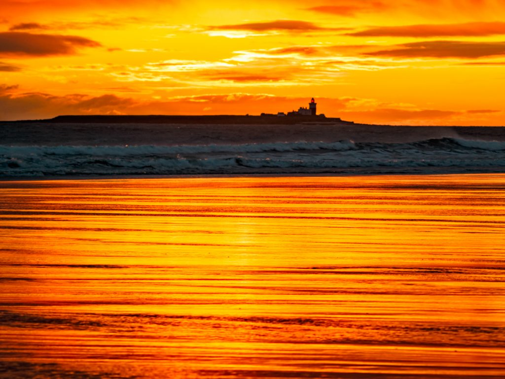 Bright yellow sunrise reflecting on the sand. Coquet Island with its lighthouse on the horizon.