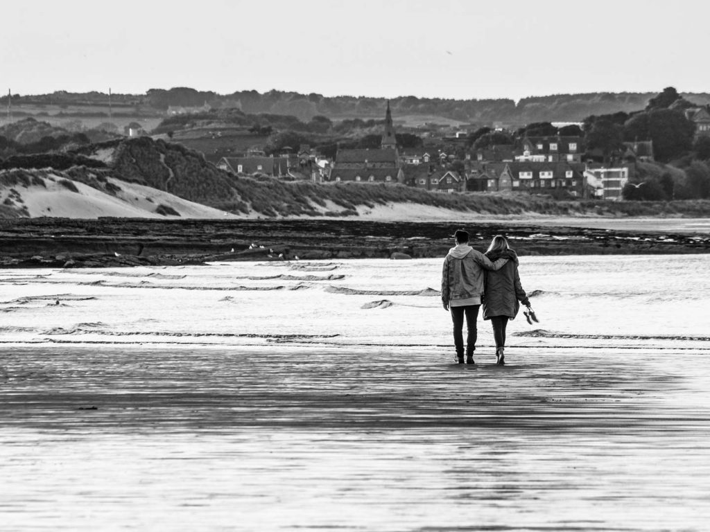 Young couple in love, walking on the beach