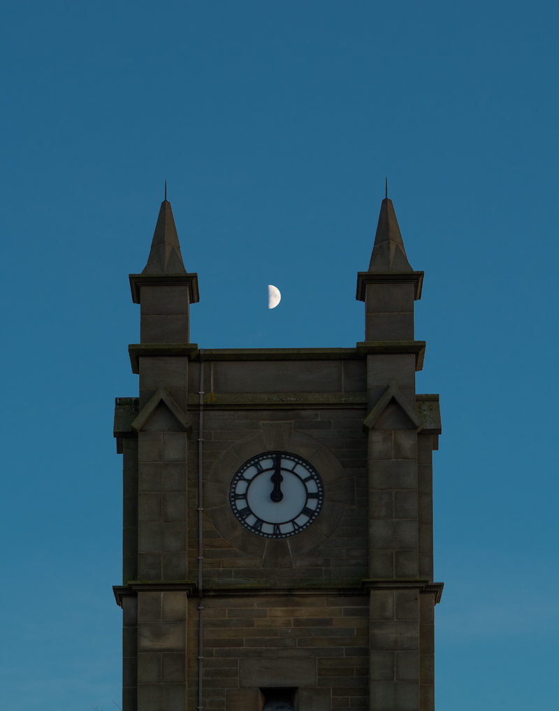 Half Moon over a clock tower at midnight