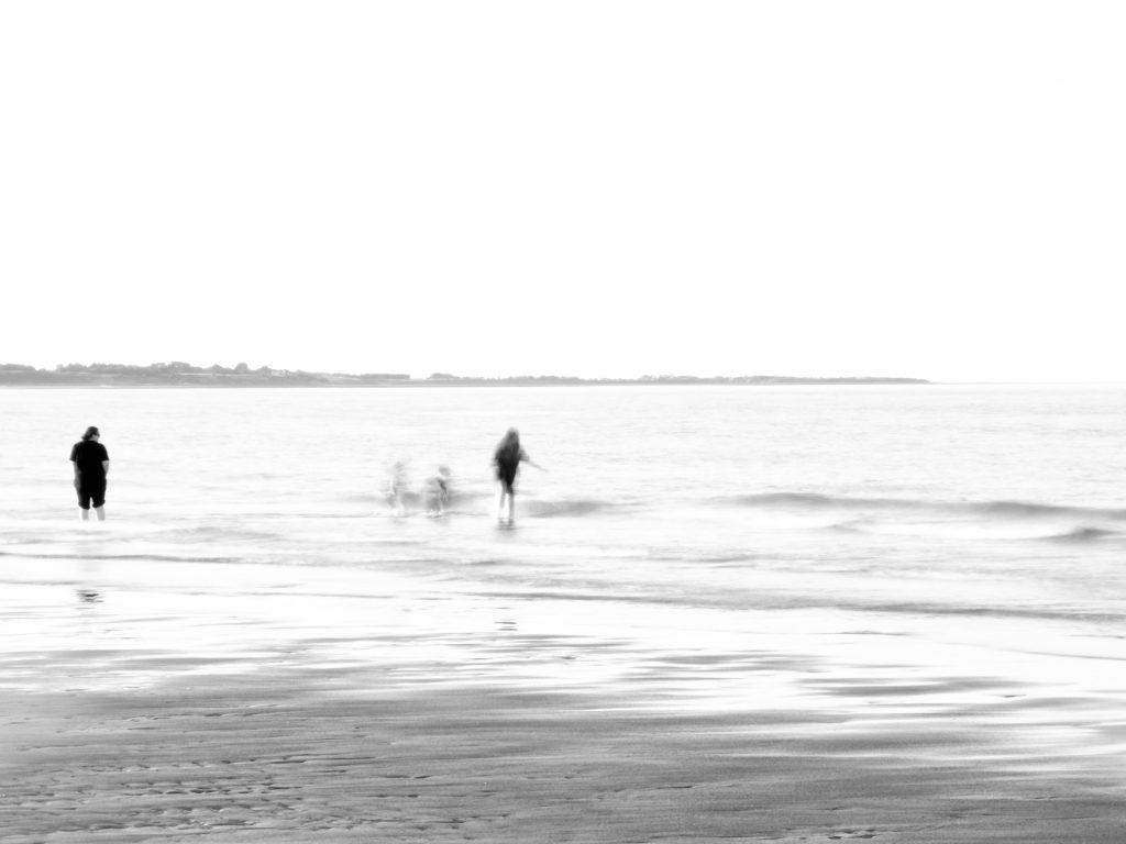 High key image with movement blur of children playing in the sea. Not shot with a camera obscura!