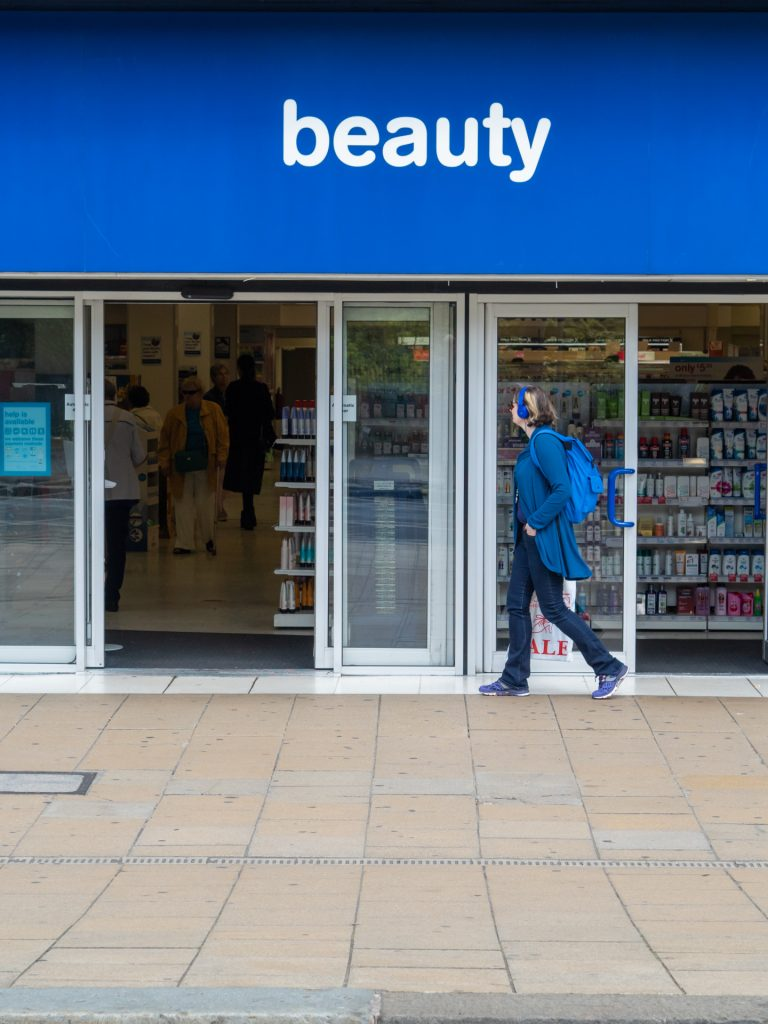 Beauty in Blue. Street Art Photography nor portraiture. A young woman walks past a shop front under a sign that says 'beauty'