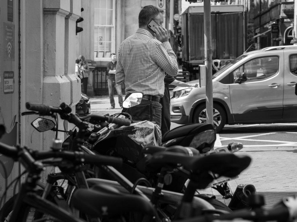 The Manager talking on his phone on a busy street.