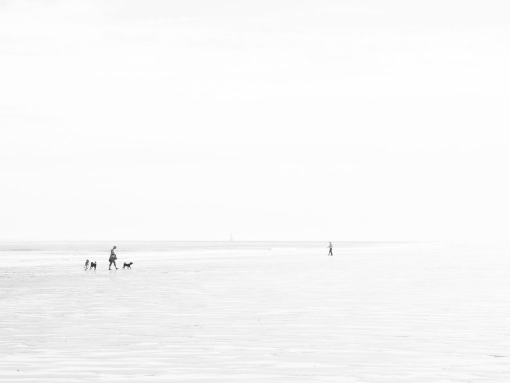 High Key - people on the beach, distant yacht in the haze