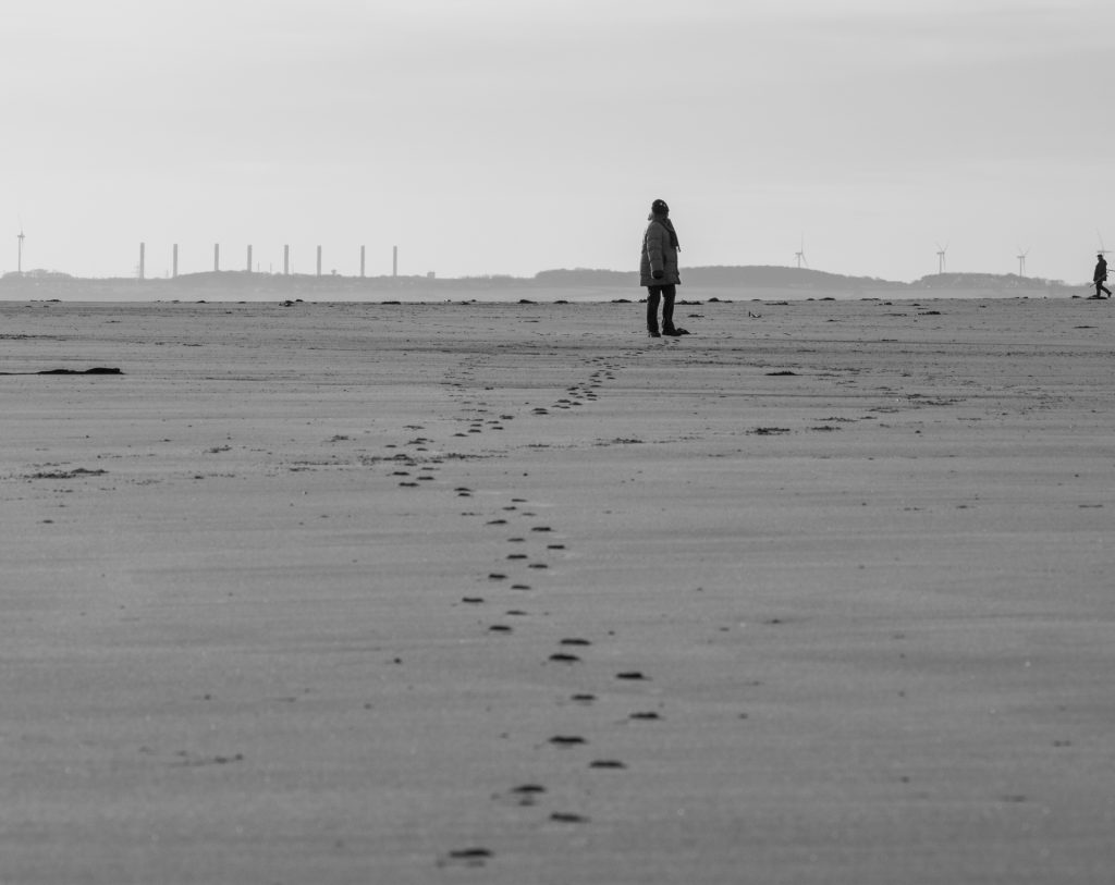 Black and white photo of a woman on the beach, uncertain of a distant figure entering the frame.
