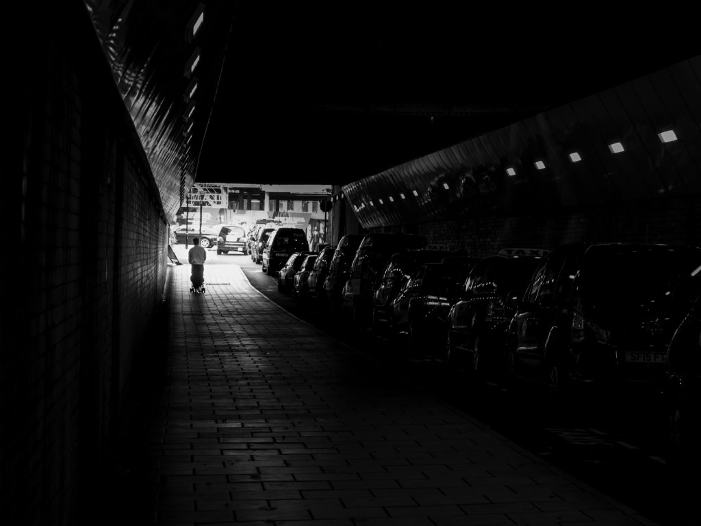 Imposters! Black and white image of a figure emerging from a dark tunnel into the light.