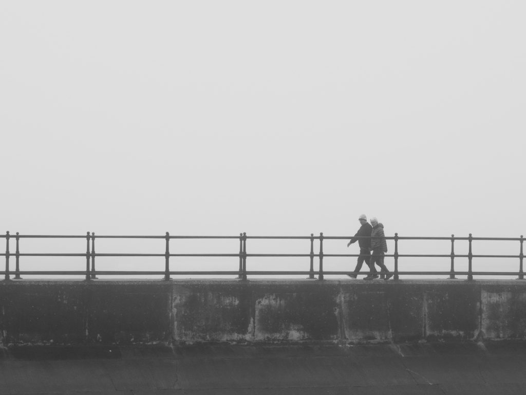 people walking on the breakwater on a foggy morning
