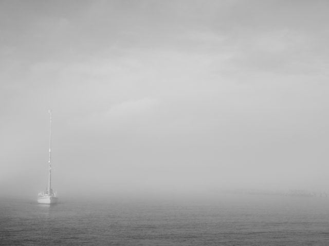 Yacht appearing out of the morning fog