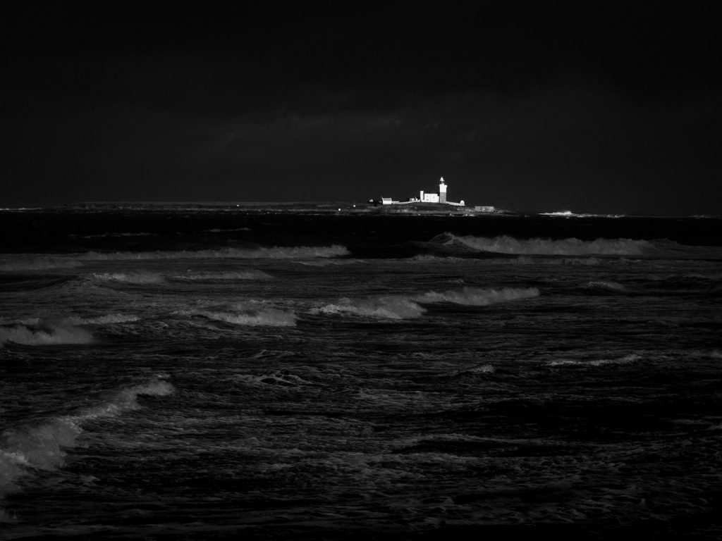 As dark storm clouds rolled overhead, the shaft of bright sunlight between them illuminated Coquet Island. Reducing the exposure emphasised the difference in tones