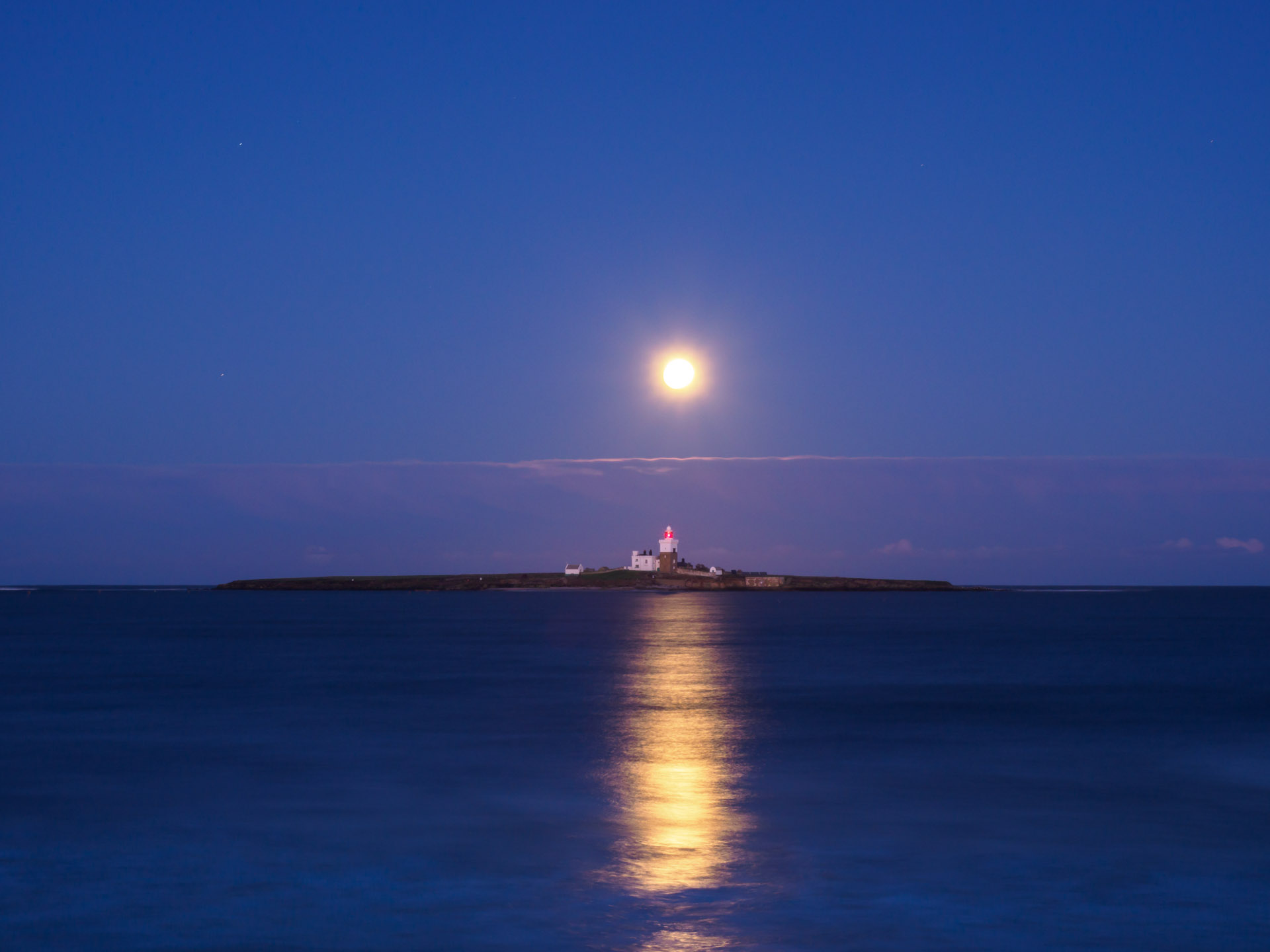 Websites Galore - Shedding a little light! Lighthouse on an island with a rising moon