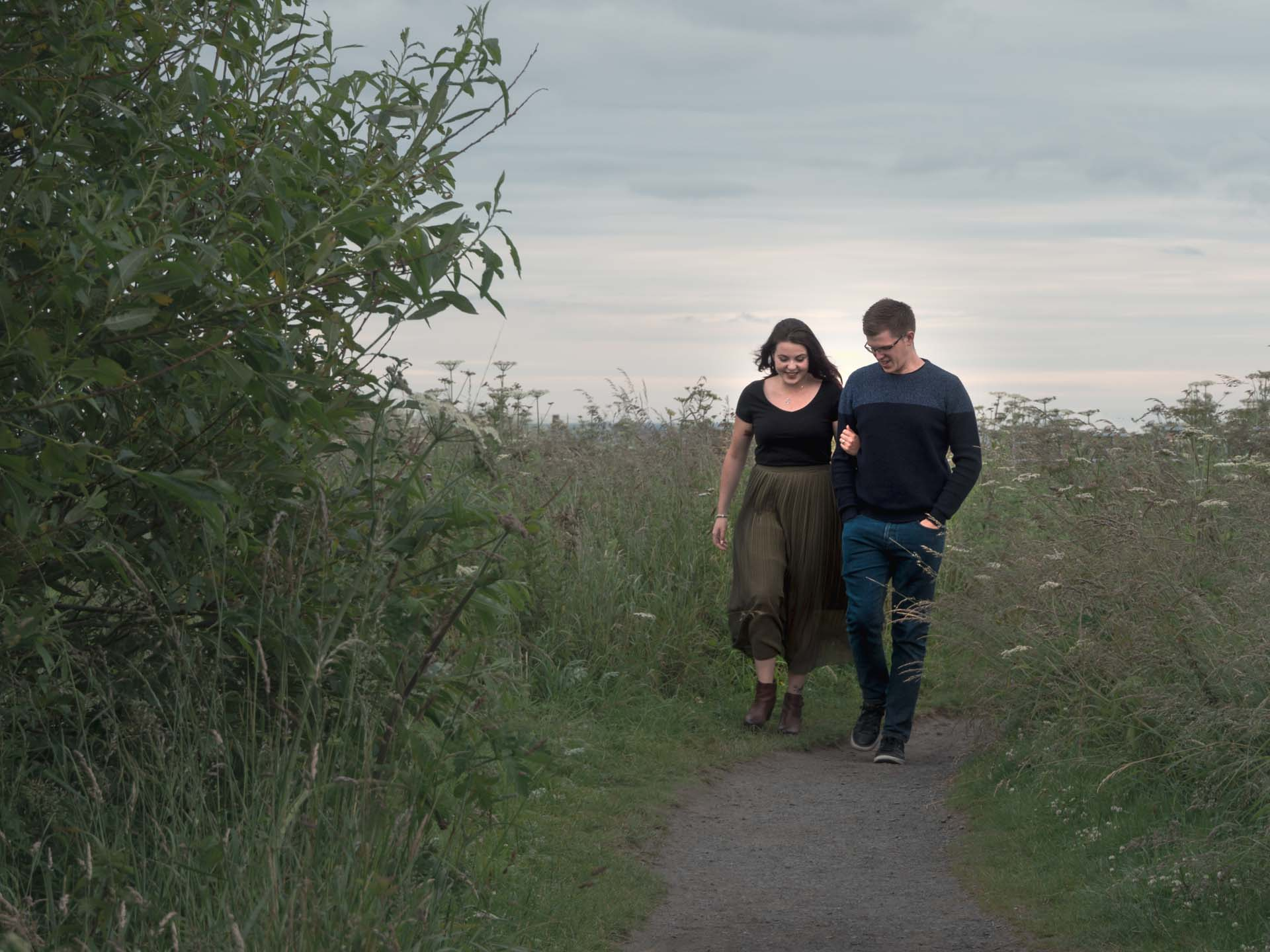 Weddings and Romantic Moments Photography. A young couple walk down a country path,